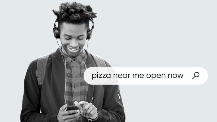 "man wearing headphones using mobile phone to search for ""pizza near me"" open now"